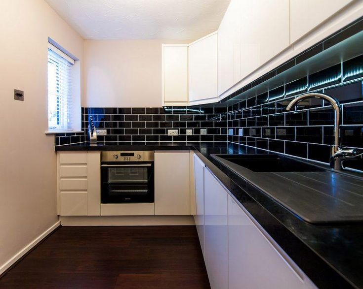 Shiny black subway tiles will glam up any kitchen backsplash. (Psst! They also won't require constant cleaning.) #kitchenbacksplash #backsplashideas #kitchendesign #blacksubwaytiles #smallkitchen