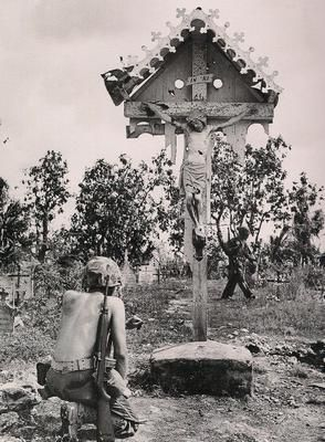 a yank kneels before a Catholic shrine in a Saipan cemetery after the Marines and Army captured the island. Prayer was needed. After 25 days of battle, some 32000 japanese were killed, and hundreds of civilians , taught to fear the coming americans , committed suicide