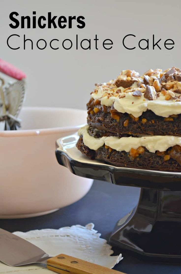 This chocolate cake has caramel and nuts baked into the layers and topped with fresh whipped cream and Snickers bars.