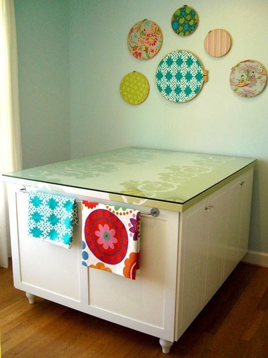 Want a work table but on a tight budget? Then check out this cost-effective Ikeahack by Kari, owner of Spring Chick Designs: She and her husband made their own custom work table for her craft room by bolting four Ikea base kitchen cabinets together and topping it off with a modified MDF table top. Don't have room for a big work table? They also created a matching desk for her sewing machine. Take a look at more photos and details after the jump...