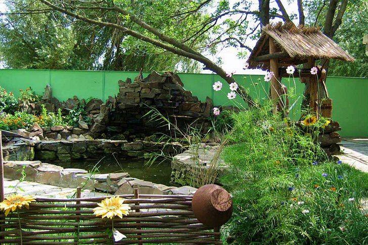 Плетеный забор, декоративный колодец, искусственный пруд - гармоничные украшения деревенского двора.