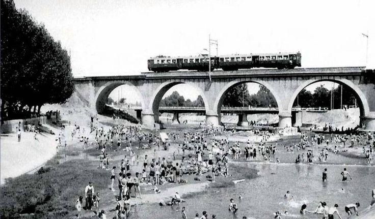 """Puente de los Franceses, Madrid (12 de enero de 1940): Imagen estival en el río Manzanares a la altura del Puente de los Franceses en los años cuarenta del siglo XX. Un """"chispa"""" circula por la línea que comunica la estación del Norte (actual Príncipe Pío) con la Sierra."""