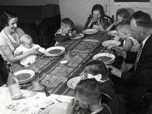 Grote gezinnen: gezin Verbeeck met 7 kinderen aan tafel, moeder houdt de baby   vast. Er staan borden soep op tafel. Plaats onbekend [België], jaartal onbekend   [1950-1965].