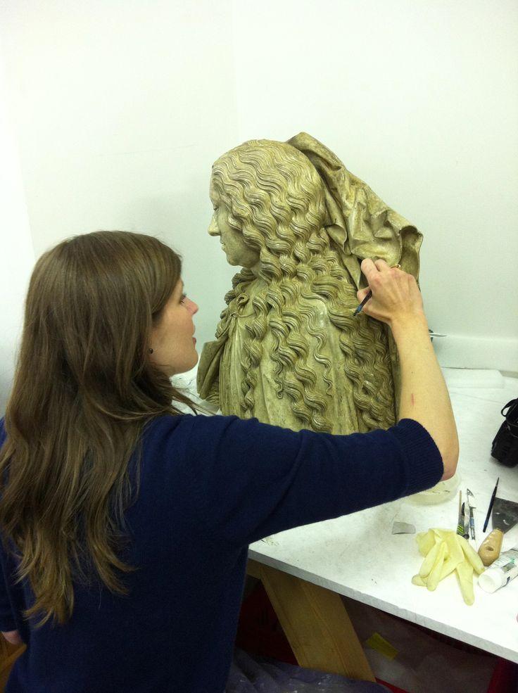 Marie Dumas, restauratrice de sculptures, retouchant la patine du moulage du buste de la statue gisante de Marguerite d'Autriche.