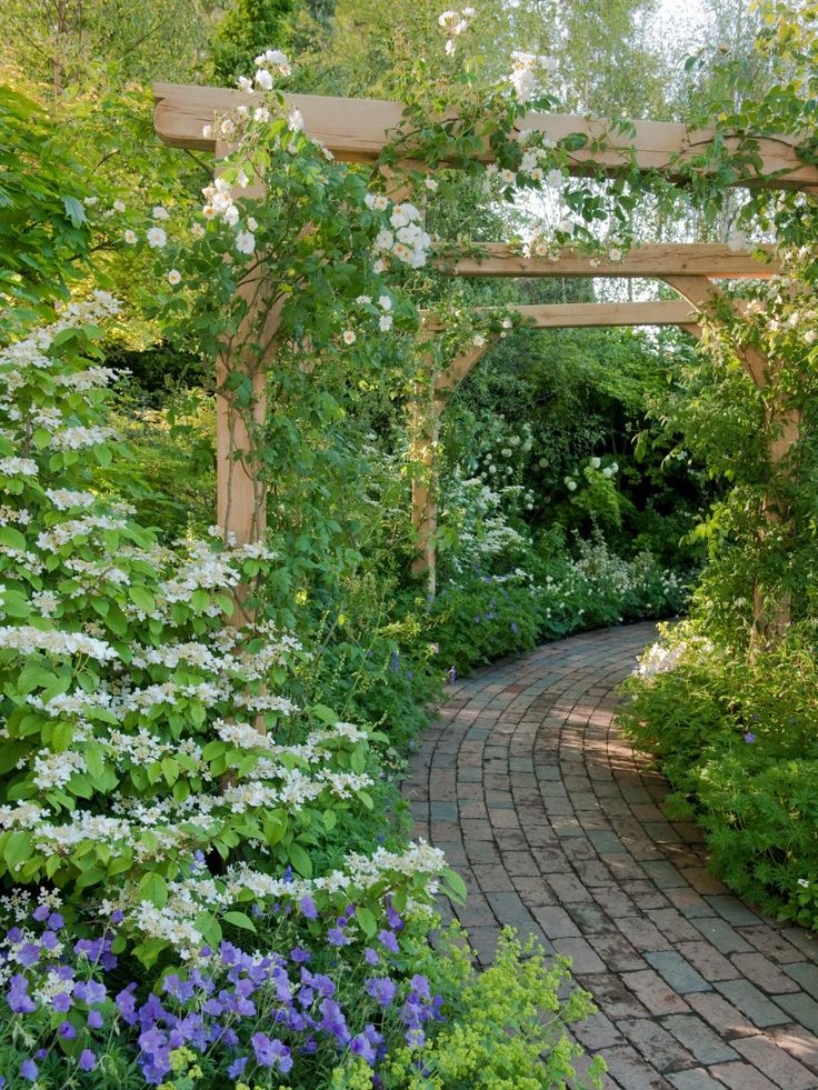 A pergola helps frame the walkway through this garden. The easy-to-navigate brick path allows maximum appreciation of the surrounding garden. To slow down the transit through your garden, narrow the path a bit. For bike traffic, keep the walkway wide and the inclines gradual.