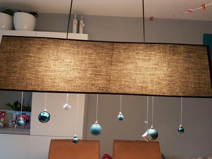 Kerstversiering aan de lamp gehangen