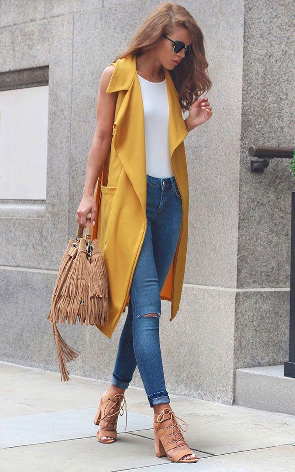 Street style look com colete amarelo e calça jeans.