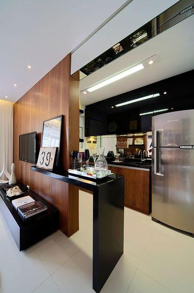 cozinha integrada com a sala de maneira inteligente com painel de madeira e mesa de pequenas refeicoes