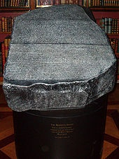 The Rosetta Stone is an ancient Egyptian granodiorite stele inscribed with a decree issued at Memphis in 196 BC on behalf of King PtolemyV. The decree appears in three scripts: the upper text is Ancient Egyptian hieroglyphs, the middle portion Demotic script, and the lowest Ancient Greek.