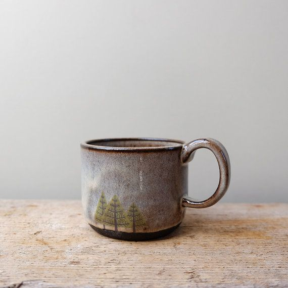 Una tazza di ceramica nera fatta a mano con rustico scuro smalti e stampa di alberi di pino disegnato a mano. Una dimensione perfetta per un caffè al mattino. È stato gettato con argilla nera nel mio studio di ceramica a Inverness rurale poi decorato con smalti di alimenti sicuri e una decalcomania disegnati a mano.  Misure Diametro--> 9 cm (3 1/2 pollici) Altezza--> 8 cm (3 1/8 pollici)  In molti dei miei pezzi in ceramica troverete piccole imperfezioni e segni lasciati dal processo di…
