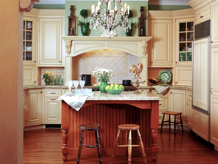 Designer Gail Drury combined traditional sage-green accents and ivory cabinets, along with contemporary materials and conveniences, to bring an updated look and feel to this charming bungalow home. An eclectic mix of wood finishes in the island and barstools further add to the kitchen's old-fashioned appeal.