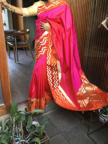 Pink banaras saree with orange border and small round buttas in blouse