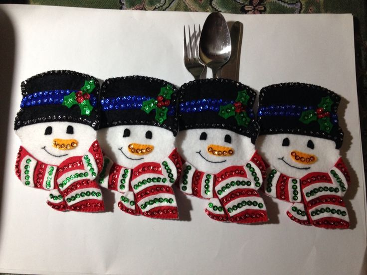 A set of four sparkly cutlery holders in the shape of snowmen.