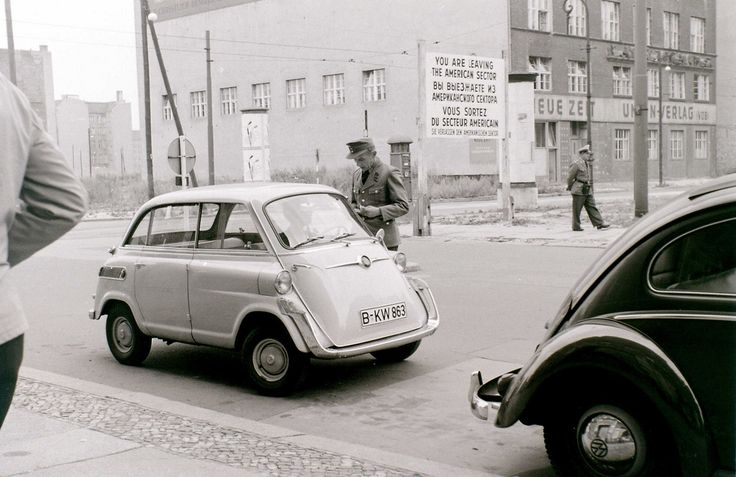 """1503 1960/7/21 Friedrichstrasse. The American border officials checking a vehicle coming from East Berlin. In the background is the famous """"Neue Zeit"""" building (in East Berlin) seen in many later Checkpoint Charlie pictures."""