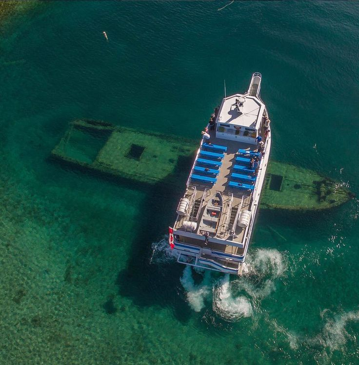 """The Great Blue Heron (125 passenger) Glass Bottom boat as it passes over the shipwreck """"The Sweepstakes"""" in Big Tub Harbour, Tobermory ON"""