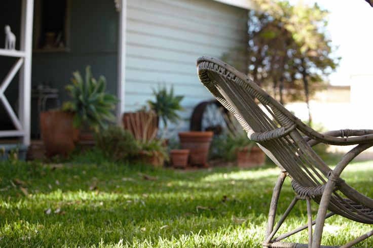 L1M1AP3 auto f/4 1/125 iso 100 73mm Object in Front of House.Low level,late afternoon.I tried to show the curve of the old garden chair up against the curves of the pots and old rim.for unity. I like the dappled light.