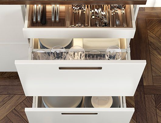 A kitchen cabinet section with open drawers showing glassware