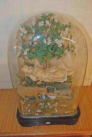 Crèche sous globe l'enfant Jésus, en cire, sous un arbre fleuri, le boeuf, l'âne et 2 moutons. Ht 52cm.