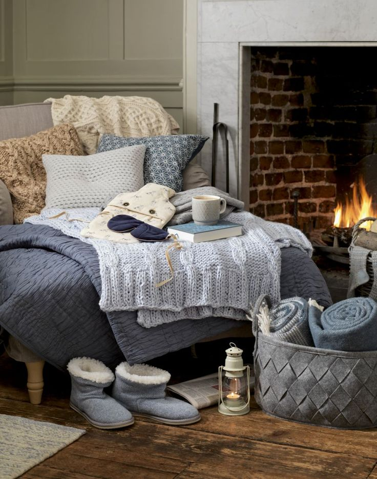 Create a cosy corner by layering throws, blankets and cushions in a similar colour palette