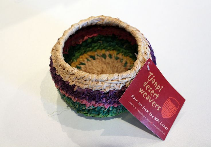 Handmade by Nellie Coulthard, Iwantja Indulkana. Measures 13cm in diameter, handwoven raffia bowl in purple, pink, green and natural colours.