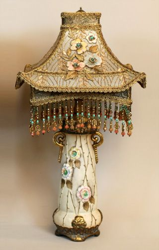 Pair of Austrian amphora bases which have been converted to lamps, hold a pair of Chinoiserie style Pagoda shades. The colors of the shades are cream and gold with accent colors of pale blue, pale pink and emerald green. The shades are covered in assorted antique metallic laces and gold lame. The applied flowers mirror the flowers in the bases. Hand beaded fringe adorns the bottom.