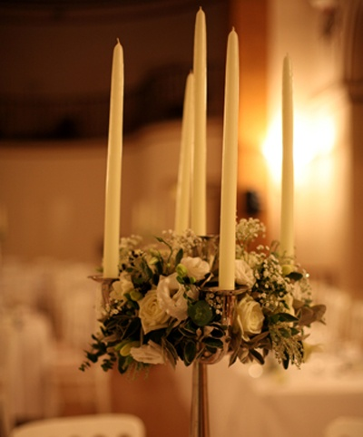 Candelabras decorated with ivory roses, freesias, lisianthus, gypsophila and foliage at The Landsdowne