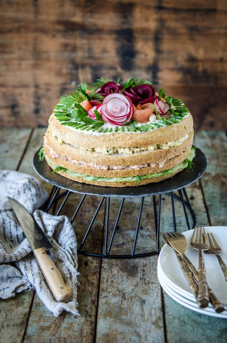 A Smörgåstårta is a savoury sandwich cake from Sweden. This recipe uses delicious fillings and clever garnishes to create a beautiful savoury cake.