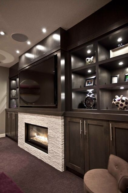 dark custom stain for the built-in maple media cabinets camouflage the TV. stand out was the fireplace, which is surrounded with a white ledgestone marble-style tile and contrasts with the dark cabinetry. @ Home DIY Remodeling