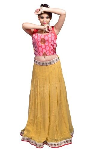 Beige chiffon lehenga embellished with kundan and paired with contrast red designer blouse.