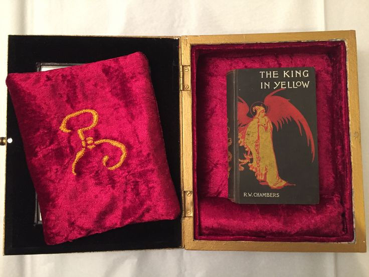 Robert Chambers, The King in Yellow. First edition, 1895. Customised display case including red velvet lining and hand embroidered yellow sign cushion to prevent light getting to the book. Display case painted in Kings yellow gold.
