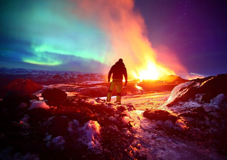 Self -portrait by James Appleton bathed in the glow of the Aurora Borealis and a volcanic eruption on the Fimmvˆruh·ls mountain pass, Iceland.