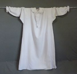 Rare Woman's Nightshirt, 18thC,  Fine white linen with deep collar with ruffled fine cotton frill continuing down the front opening, three linen covered buttons, the wide sleeves gathered into cuff bands with similar frills, wide gores to the sides, 54 in or 1.37 m shoulder to hem. English Costume | Meg Andrews - Antique Costumes and Textiles