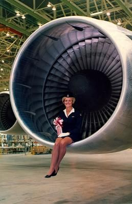 On hand at the Boeing factory in Everett, Washington state, was Carol Hardy, normally found on Boeing 707s but as BOAC ambassadress she sportingly perched on the nine-foot intake of the enormous 747's Pratt & Whitney engine. - Daily Telegraph. (This was to try it for size so that future air hostesses could also pose there. It was a mega improvement over the 1st generation jet engines!