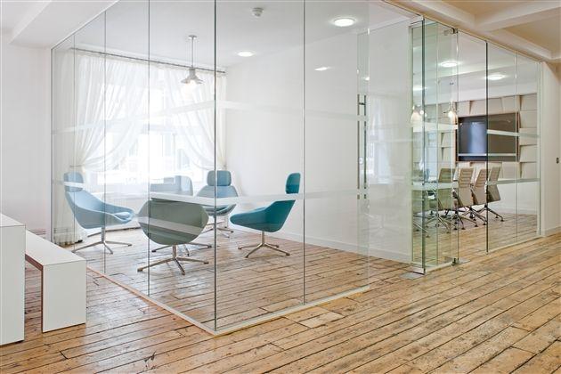 Gaaf contrast tussen de houten vloer en design inrichting in combinatie met de kleur wit bij deze vergaderruimte in Londen
