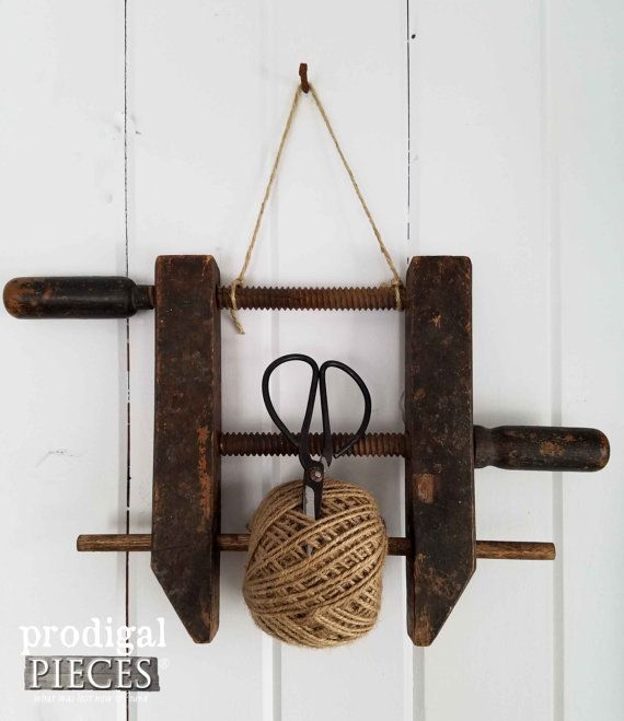 Add farmhouse chic flair to your decor with antique handmade wooden clamp turned into a twine holder. This clamp has a gorgeous time-worn patina with added dowel for twine. Comes with ball of twine (shears not included) Use the holder in your office, kitchen, art room, and more. A perfect addition to your rustic, farmhouse, modern chic, industrial, shabby, cottage chic, flea market, or vintage eclectic décor. Dimensions: 14 L x 3 W x 13 H  Please take a minute to peruse the other vintage and…