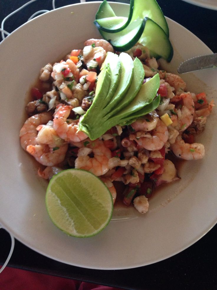 Shrimps octopus and fish with guacamole and a pice of lemon