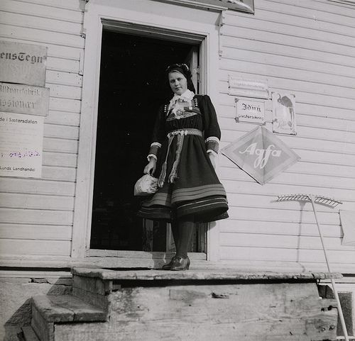 Meyer, Elisabeth Woman in a Setesdal-costume at the stairs of a shop. Photographs from Setesdal around 1940-42. Gelatin silver print, baryta