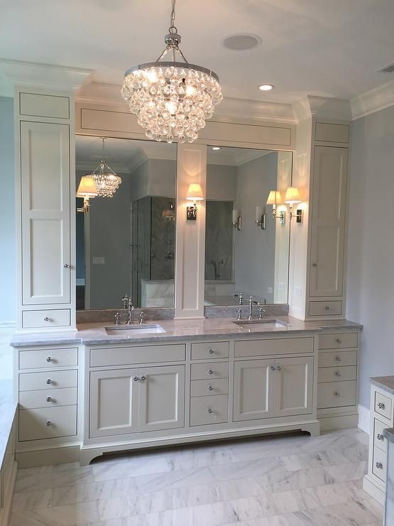 Ivory master bathroom features a Robert Abbey Bling Chandelier illuminating ivory cabinets topped with gray marble fitted with his and hers sinks under inset mirrors.