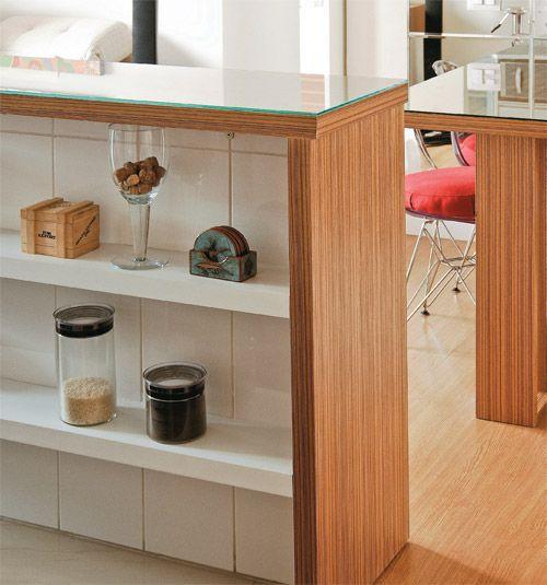 O balcão que integra sala e cozinha revela um truque e tanto: um nicho azulejado com 15 cm de profundidade, cortado por duas prateleiras de MDF revestido de melamina branca. Ali ficam potes de mantimentos. Placas de vidro transparente cobrem a mesa de jantar e o balcão, revestidos com lâmina de madeira no padrão Teak 93Q, da Rume. A solução facilita a limpeza das superfícies e dá unidade visual à sala. As banquetas com assento transparente deixam a ambientação mais leve. A regulagem de…