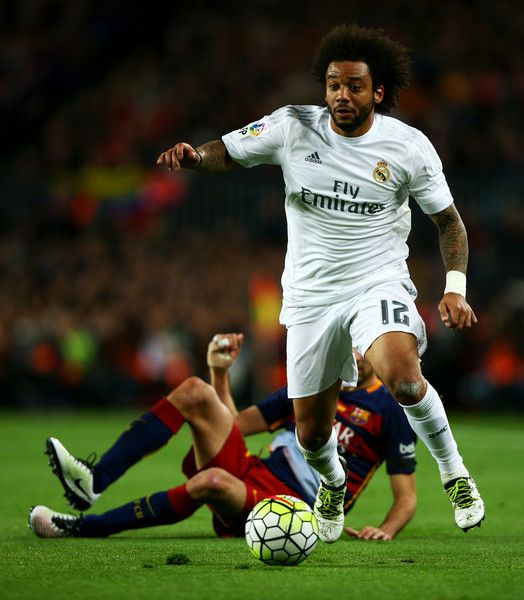 Sergio Busquets of FC Barcelona slides in on Marcelo of Real Madrid CF during the La Liga match between FC Barcelona and Real Madrid CF at Camp Nou on April 2, 2016 in Barcelona