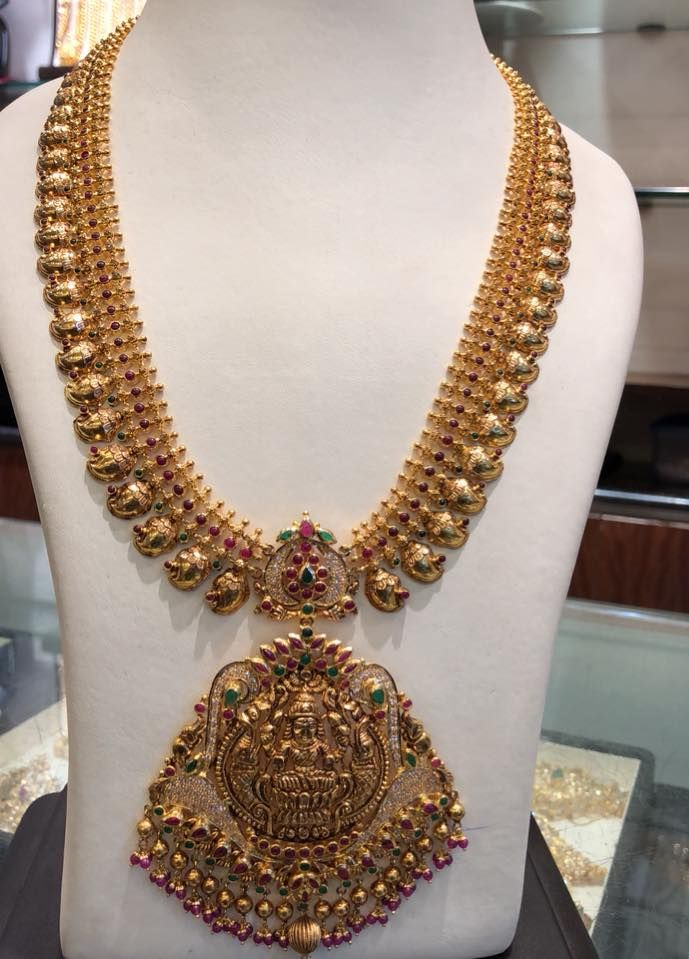 Stunning gold long haaram with mango hangings. Long haaram having lakshmi devi pendant. Long haaram studded with multi color precious stones. 17 March 2018