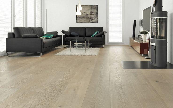 pavimento in parquet chiaro in un salotto ampio con divani neri