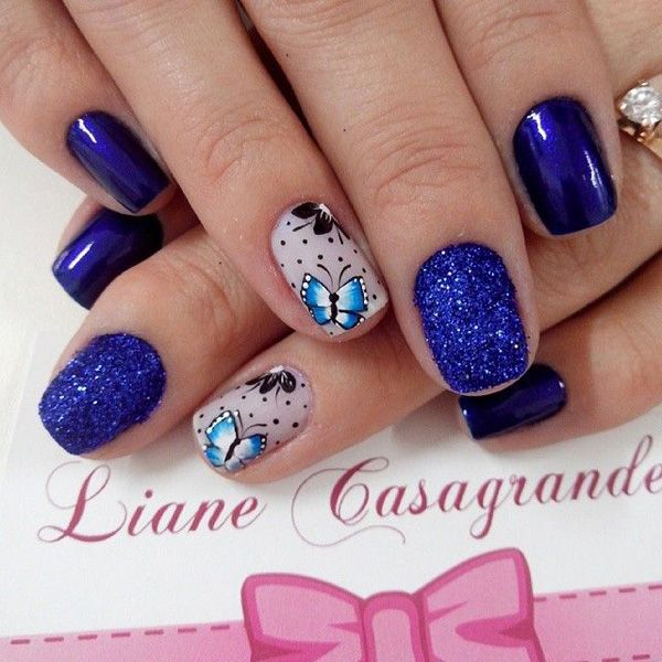 A cool looking butterfly inspired nail art design. The nails are painted with royal blue and blue gray polish as base colors. Atop the blue gray nails rests pretty butterflies in light blue polish with black polka dots surrounding them. The nails are also painted in royal blue sparkles for effect.