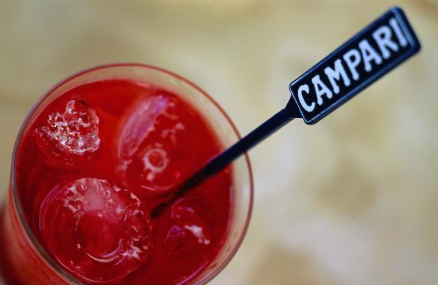 Explore the Bitterness of Campari: A Campari swizzle stick sticking out of a glass of Campari and soda in a bar - Noosa, Queensland