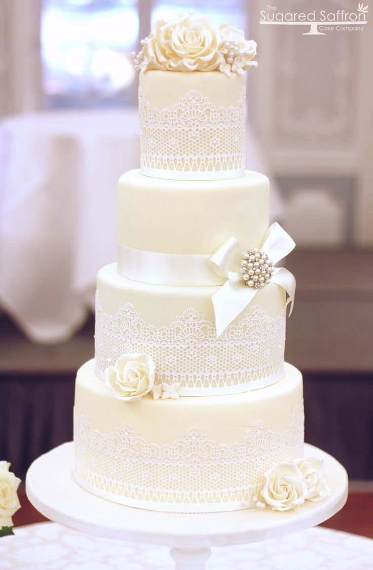 Four tier cake in ivory with white edible cake lace by the Sugared Saffron Cake Company