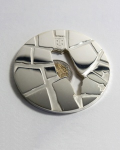 "Jennifer Hoes , ""Hole in the Market ', medal, silver with hand carvings by Daniel Houwer, 2011"