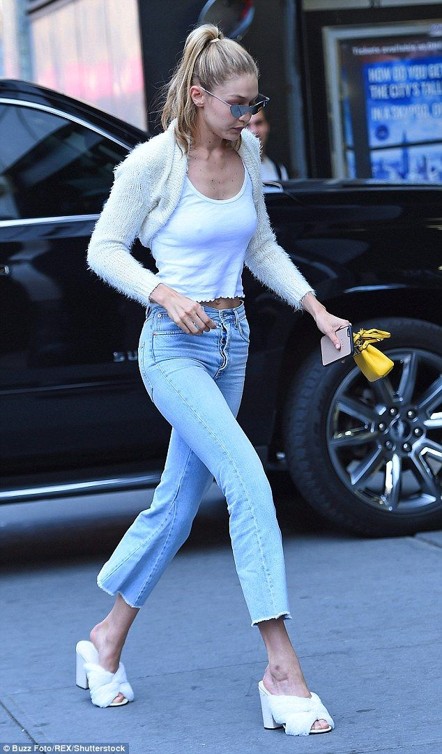 Ready for the catwalk: Gigi added blue jeans cut off at the calf and a pair of white fluffy mules for her outing