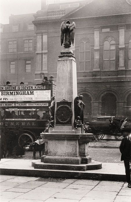 Drinking fountain opposite the Royal London Hospital, Whitechapel, and erected in 1911 to commemorate the life of King Edward VII. The monument was from members of the Jewish community. The statuary was originally cast in bronze; but this was stolen so often that it has long since been replaced by casts in a cheaper material. Designed by William S. Frith. (This photo is c. 1920 + shows a No. 8 London omnibus)