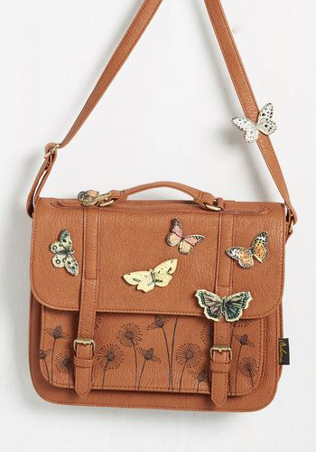 Show all the other bags who's who with this cognac brown satchel. With it's structured faux-leather fabric and sandy-brownouter pocket with floral tooling, this crossbody purse will quickly earn its place in the top tier of everyday accessories!