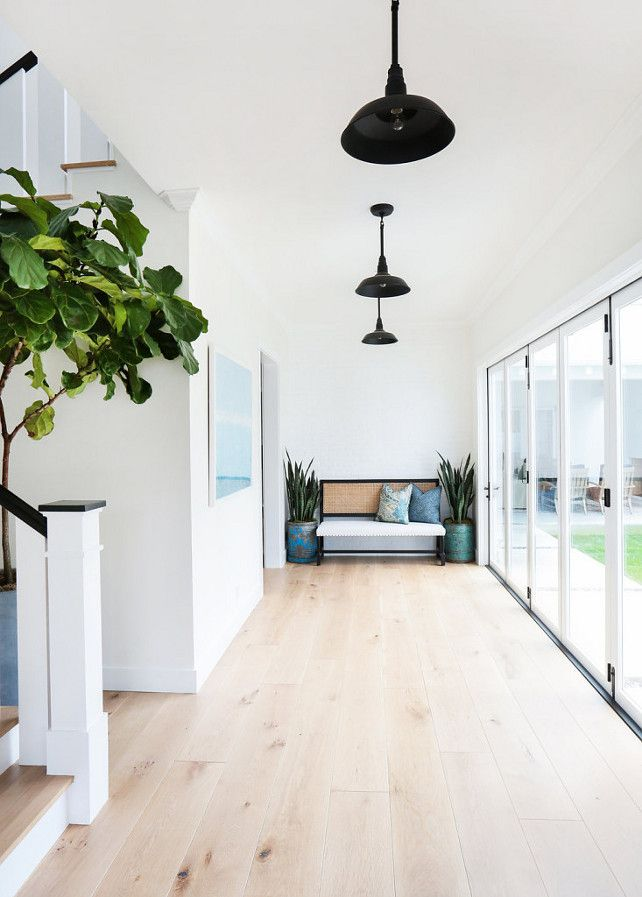 Modern Farmhouse with Transitional Interiors. Foyer: The foyer has a very airy and open feel thanks to the walls painted in a warm white, folding patio doors and the wide whitewashed plank hardwood floors.